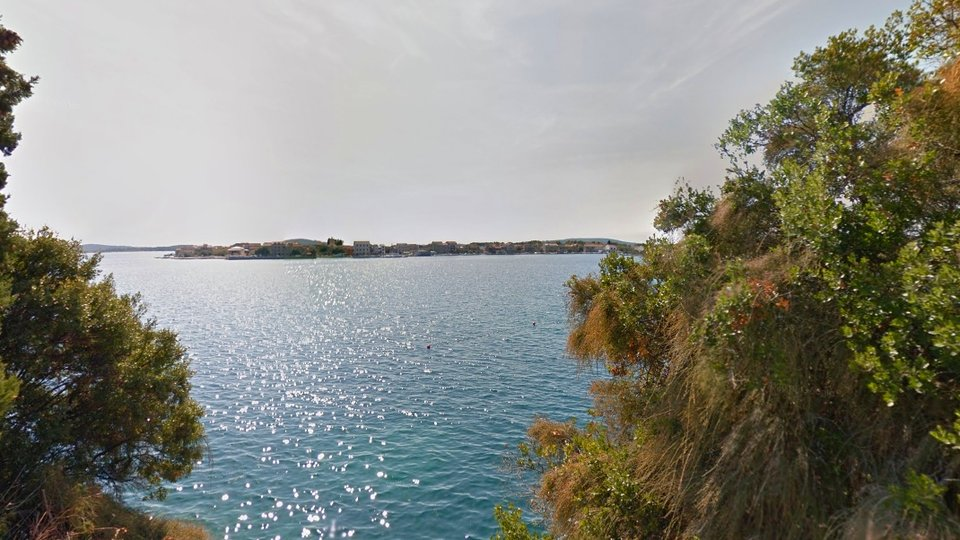 Beautiful land with an old house in the first row to the sea in an exclusive location in Brodarica